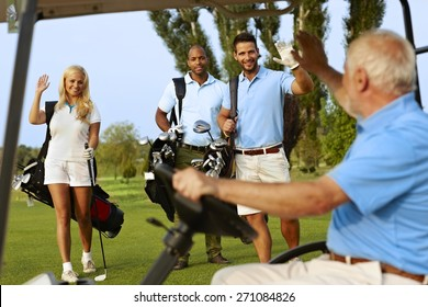 Golfers greeting on golf course, waving, smiling.
