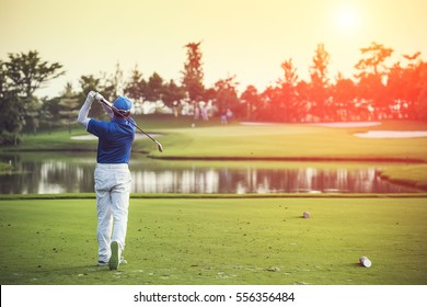 Golfers hit sweeping golf course from fairway at sunrise vintage tone