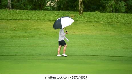 Golfers walking under umbrella on green grass.