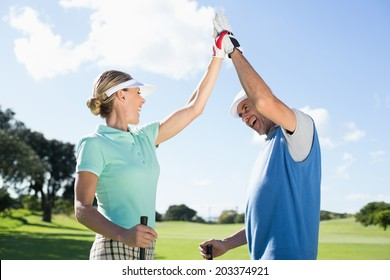 Golfing couple high fiving on the golf course on a sunny day at the golf course