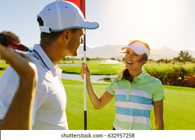 Golfing couple on the putting green at the golf course. Male with golf stick and female holding flag.