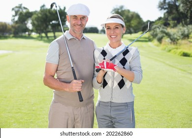 Golfing couple smiling at camera holding clubs on a sunny day at the golf course