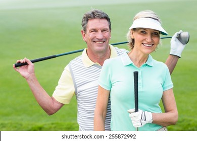 Golfing couple smiling at camera holding clubs on a foggy day at the golf course