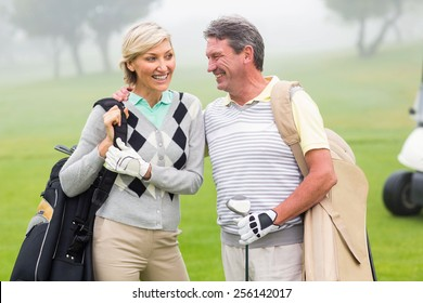 Golfing couple smiling and holding clubs on a foggy day at the golf course