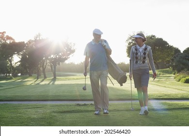 Golfing couple walking and chatting on a sunny day at the golf course