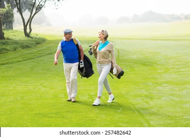 Golfing couple walking on the putting green on a foggy day at the golf course