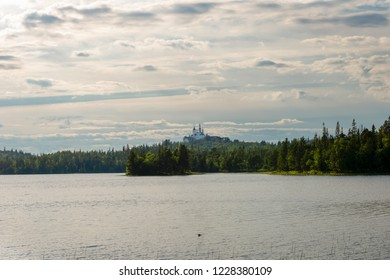 Golgofo-Raspyatsky skete, the Holy lake and the swan. Anzer island, Solovetsky archipelago, Russia