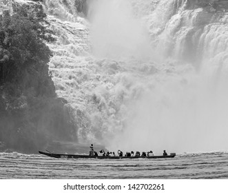 Golondrina falls and tourists boat in the lagoon of Canaima national park - Venezuela, Latin America (black and white)