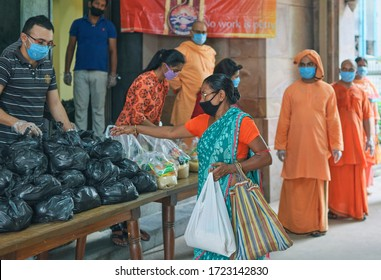 Golpark, Kolkata, 5/5/2020: Poor people collecting everyday essentials from monks and volunteers, in a humanitarian effort by Ramakrishna Mission Golpark. Monks are seen in traditional saffron dresses