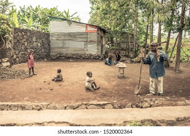 Goma / Democratic Republic of the Congo – October 12, 2016: group of children sitting on the floor and playing next to metal house and man holding shovel and other tools on the outskirts of Goma