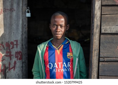 Goma / Democratic Republic of the Congo – October 13, 2016: Portrait of a boy wearing a fake shirt of the Futbol Club Barcelona at the door of a wooden shed during sunrise in the outskirts of Goma