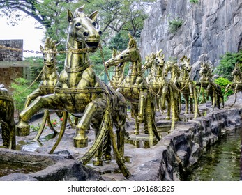 Gombak, Malaysia - 10/9/2016: A team of twelve bronze horses pull Vishnu's chariot and stand at the entrance to the Ramayana Cave at the Batu Cave Complex.