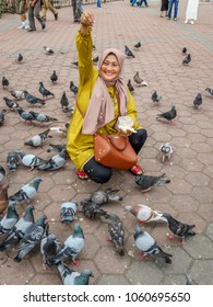Gombak, Selangor, Malaysia - 10/9/2016: A Malaysian Muslim woman feeds pigeons at the courtyard before the Batu Caves comple.