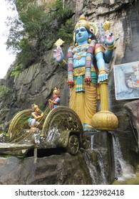Gombak / Selangor / Malaysia - November 2017: Statue of Krishna next to entrance to Hindu shrine in Ramayana Cave at the Batu Caves complex.