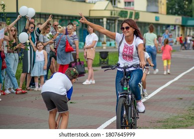 Gomel, Belarus, 18.08.20: Peaceful protests in Belarus. Presidential elections in Belarus 2020. A girl on a bicycle in a T-shirt with Belarusian symbols waves to protesters