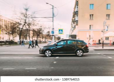Gomel, Belarus - April 16, 2019: Black Lada Vesta SW Cross Car Fast rides down City Street. Side View