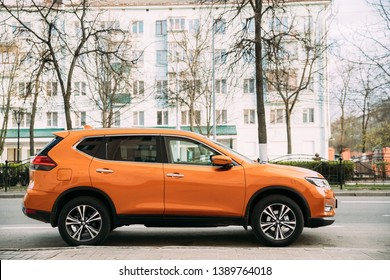 Gomel, Belarus - April 16, 2019: Orange Nissan X-Trail third generation Car Parked At Street. Side View
