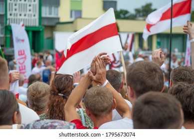 Gomel, Belarus, August 26,2020: A man claps his hands against the background of the Belarusian flag. Rally for freedom. Elections in the Republic of Belarus. Free peaceful people.