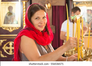 GOMEL, BELARUS - AUGUST 8, 2014: a girl in the Orthodox Church lights candles