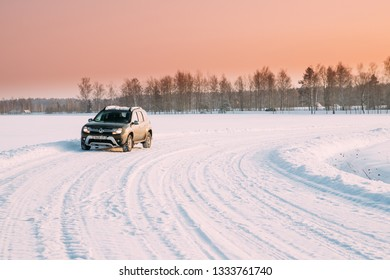 Gomel, Belarus - January 10, 2019: Car Renault Duster Or Dacia Duster Suv Parked On Winter Snowy Field Countryside Landscape Under Scenic Sky At Sunset Dawn Sunrise.