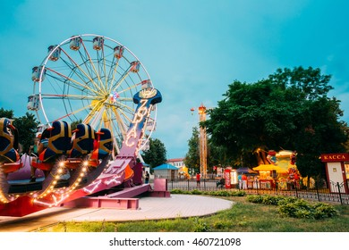 Gomel, Belarus - July 17, 2016: The Attraction Feature Zodiac With People On Seats Going To Start. The Ferris Wheel, Tower Attraction On Summer Evening Blue Sky And Tree Background.