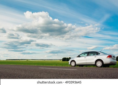 Gomel, Belarus - June 13, 2016: Volkswagen Vento Polo car parked on the side of the road against the beautiful cloudy blue sky and green field in the countryside