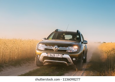 Gomel, Belarus - June 21, 2018: Renault Duster or Dacia Duster SUV in country road through summer wheat field. Duster produced jointly by French manufacturer Renault and its Romanian subsidiary Dacia