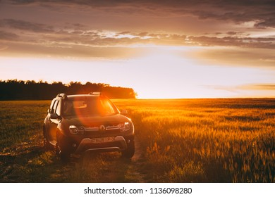 Gomel, Belarus - June 22, 2018: Renault Duster Or Dacia Duster Suv In Road Through Summer Wheat Field In Amazing Sunset Time. Duster Produced Jointly By French Manufacturer Renault
