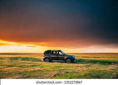 Gomel, Belarus - June 22, 2018: Car Renault Duster Or Dacia Duster Suv In Road Through Summer Wheat Field In Amazing Sunset Time. Duster Produced Jointly By French Manufacturer Renault