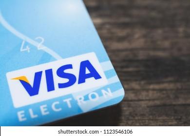 GOMEL, BELARUS - June 30, 2018. Visa logos on credit cards. Wood background.