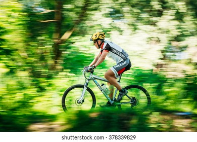 GOMEL, BELARUS - JUNE 7, 2015: Aged Mountain Bike cyclist riding track at sunny summer day, healthy lifestyle active athlete doing sport. Motion blur green grass and trees background