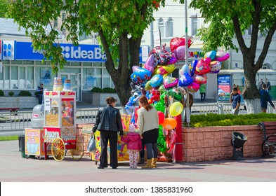 GOMEL, BELARUS - MAY 1, 2016: Unknown women with children are on city street near place of sale of cotton candy, popcorn and colorful balloons, Gomel, Belarus