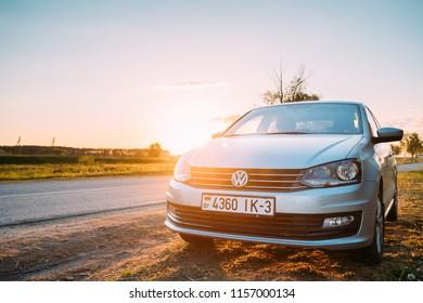 Gomel, Belarus - May 16, 2017: VW Volkswagen Polo Vento Sedan Car Parking Near Asphalt Country Road In Sunny Sunset. Sunlight Above Road In Sunrise.