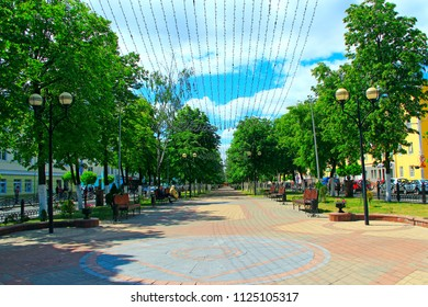Gomel / Belarus - May 20, 2018 : Street of Belarusian city of Gomel with benches trees and hanging garlands. People resting in park with benches and garlands. People relax in city. Beautiful city park