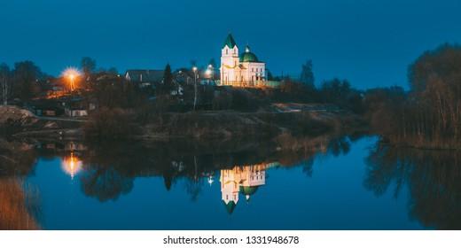 Gomel, Belarus. Panorama Of Church Of St Nicholas The Wonderworker In Lighting At Evening Or Night Illumination. Landscape With Orthodox Church Of St. Nikolaya Chudotvortsa, Reflection In Sozh River
