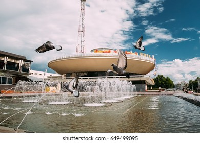 Gomel, Belarus. Pigeons Doves Are Flying Over A Fountain Near Gomel State Circus In A Summer Sunny Day. Famous Local Landmark Under Sunny Blue Sky In Summer Day