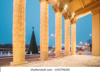 Gomel, Belarus. View Of Xmas Christmas Tree Through Column Of Gomel Regional Drama Theatre On Lenin Square At Evening Or Night Illuminations Lights. Famous Place At Winter New Year Holiday Season.