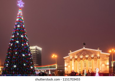 Gomel Drama Theater in festive illumination and a city tree in the square of the city of Gomel