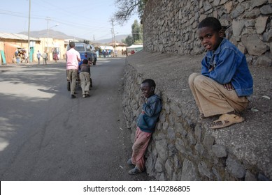 GONDAR, ETHIOPIA - MARCH 25 2012: Unidentified small beggars wait for tourists by Fasilides Castle in Gondar, Ethiopia. Begging is common for Ethiopian children near tourist sites in Gondar.