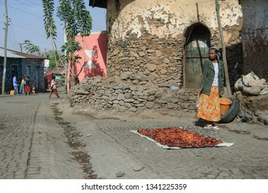 GONDAR, ETHIOPIA - MARCH 25 2012: Unidentified Ethiopian woman dries chili pepper on a street of Gondar, Ethiopia. Red chili pepper is widely used in many Ethiopian dishes.