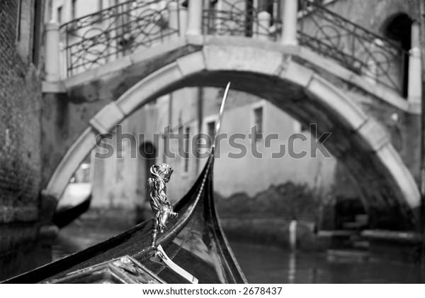 A gondola about to go underneath a bridge on a Venice canal