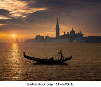 Gondola by Saint Mark square during sunrise with San Giorgio di Maggiore church in the background in Venice Italy