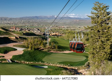 Gondola cables and three cabins suspended over a golf course. Canyons resort, Park City, Utah.