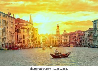 Gondola with gondolier near Rialto Bridge Grand Canal in Venice, Italy during sunset. Venice postcard. Tourism concept.