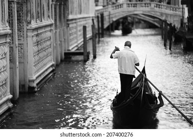 Gondola with gondolier on a channel in Venice, Italy
