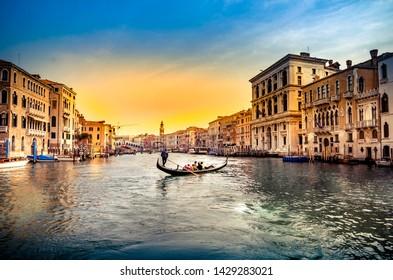 Gondola near Rialto Bridge in Venice, Italy at sunset