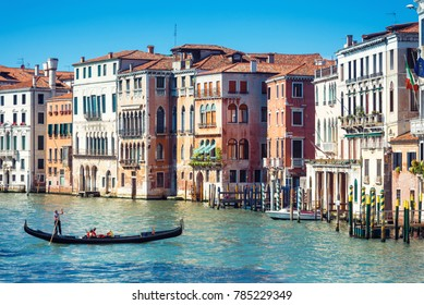 Gondola with tourists is sailing along the Grand Canal in Venice, Italy. Water trip on a gondola in Venice. Romantic travel across Venice. Scenic panoramic view of sunny Venice.