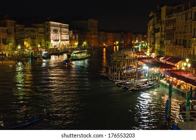 Gondolas floating on water in the city at night.