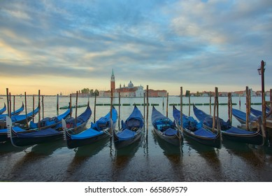 Gondolas in front of the San Giorgio Maggiore church in Venice at sunrise