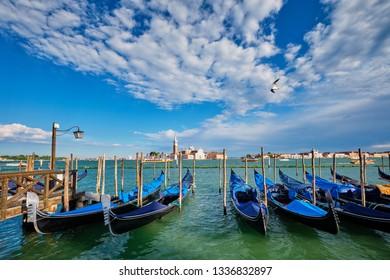 Gondolas and in lagoon of Venice by Saint Mark (San Marco) square with San Giorgio di Maggiore church in background in Venice, Italy